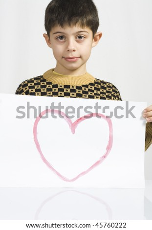 Young boy showing off drawing of heart. - stock photo