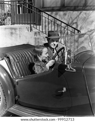 Young boy sitting in the driver's seat of car with his father - stock photo