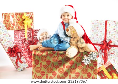 Young boy sitting on christmas gifts - stock photo