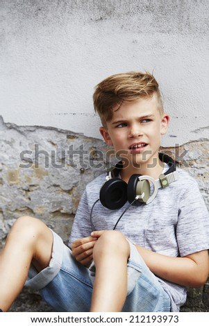Young boy sitting on ground wearing headphones  - stock photo