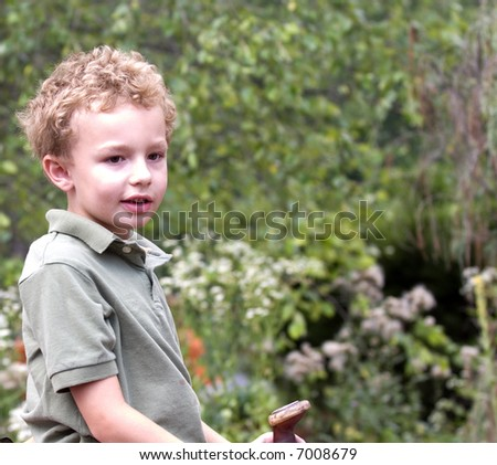 Young boy sitting on saddle outdoors - stock photo
