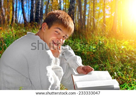 young boy sitting with a book in the autumn forest - stock photo