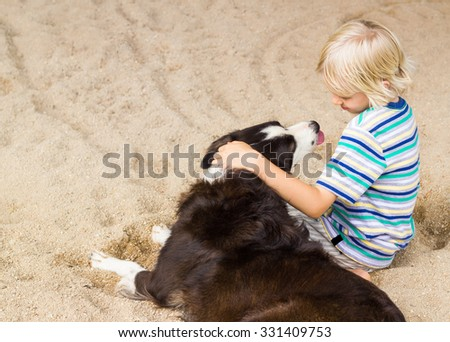 Young boy sitting with arm around his pet dog at the beach - stock photo
