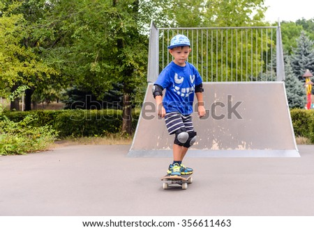 Young boy skateboarding at the park coming towards the camera from the foot of a ramp with a look of concentration as he learns to balance - stock photo