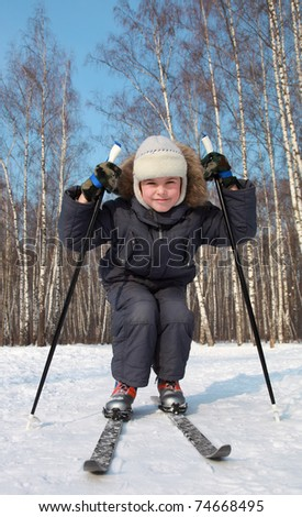 Young boy skates on cross-country skis inside winter forest at sunny day - stock photo