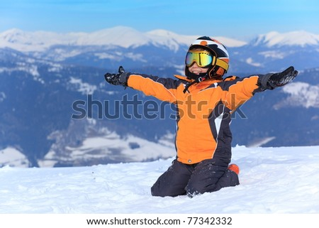 Young boy skier sitting in snow with arms stretched out. - stock photo
