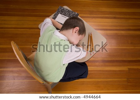 Young boy sleeping at school desk with book and pencils in a wood floored classroom - stock photo