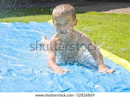 Young boy sliding on a water slide in the back yard - stock photo