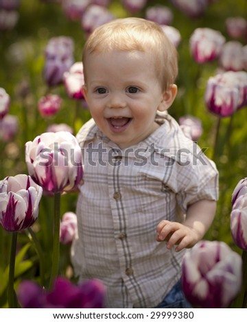 Young Boy Smiling in a Tulip Patch - stock photo