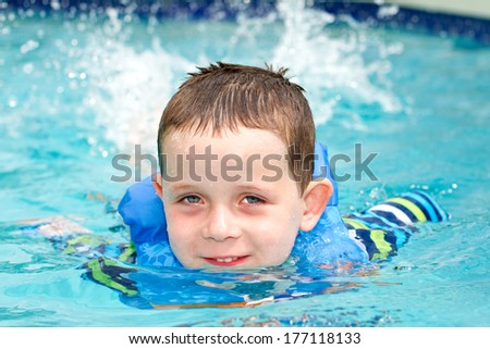 young boy smiling whilst swimming in the pool - stock photo