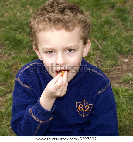 Young boy snacking orange puffs while sitting outside - stock photo