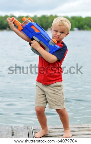 Young Boy Sneers with Water Gun - stock photo