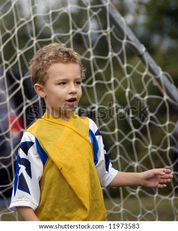 Young boy soccer player standing in front of goal net - stock photo