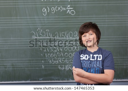 Young boy solving a maths problem in class standing with a piece of chalk in his hand in front of the blackboard covered in numbers - stock photo
