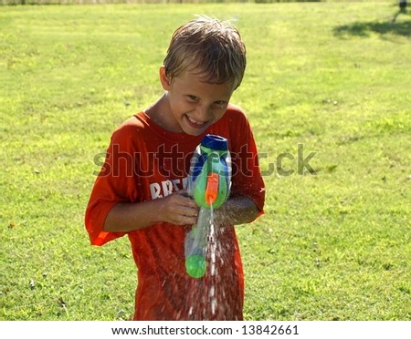 young boy squirting a gun at photographer - stock photo