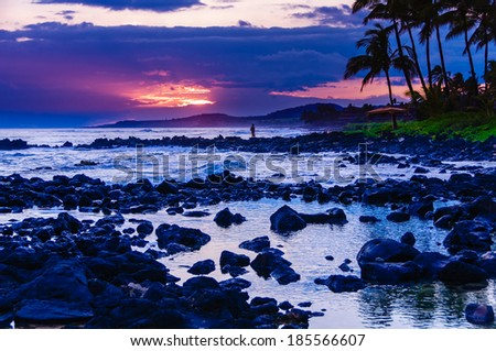 Young boy standing on a rocky outcrop on a beach at sunset in Hawaii. - stock photo