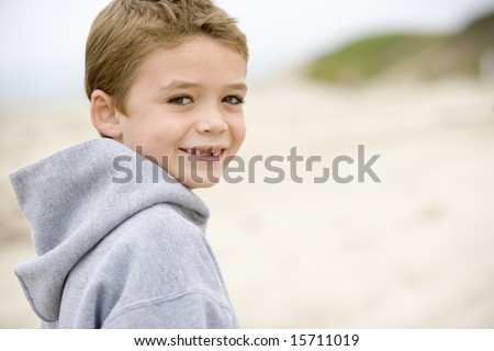 Young boy standing on beach smiling - stock photo