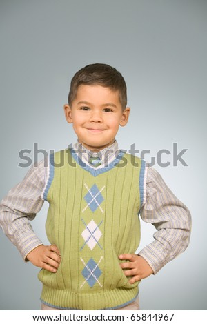 Young boy standing with hands on hips - stock photo