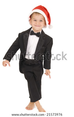 Young boy standing with tuxedo on and Santa hat. Isolated on white. - stock photo