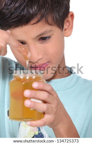 Young boy tasting some honey - stock photo