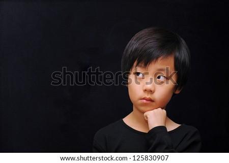 Young boy thinking  ( dark background ) - stock photo