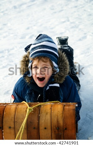 young boy tobogganing - stock photo