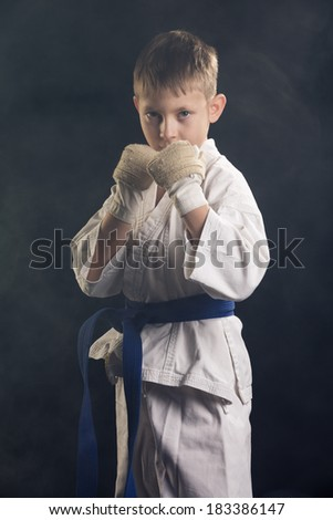 Young boy training karate. Black background - stock photo