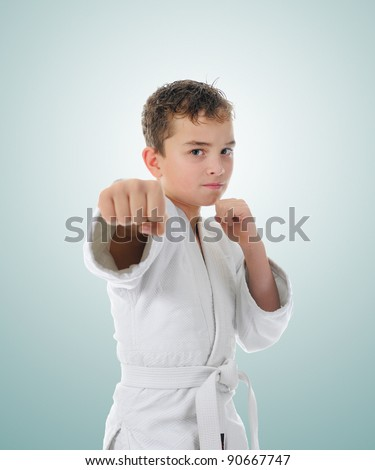 Young boy training karate. on green background - stock photo