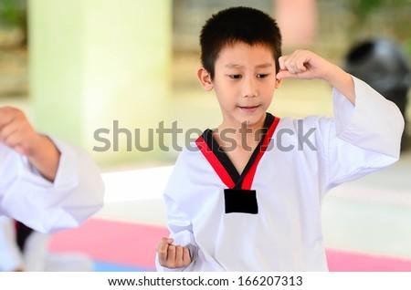 Young boy training taekwondo action - stock photo