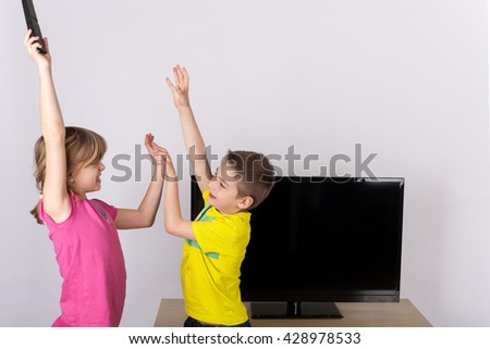 Young boy trying to get the tv remote control from his sister - stock photo