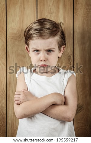 Young boy trying to look tough - stock photo