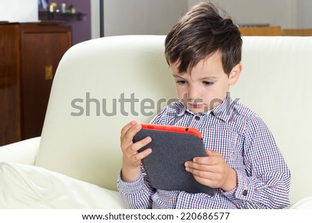 Young boy using a tablet computer. - stock photo