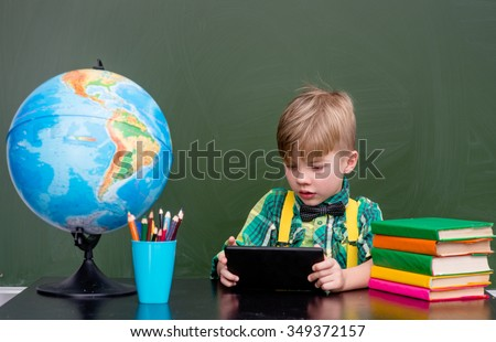 Young boy using tablet computer in classroom - stock photo