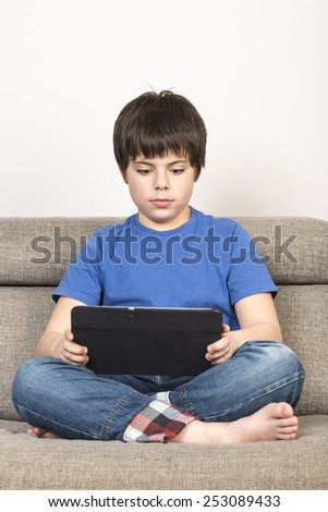 Young boy using tablet digital on the sofa.  - stock photo