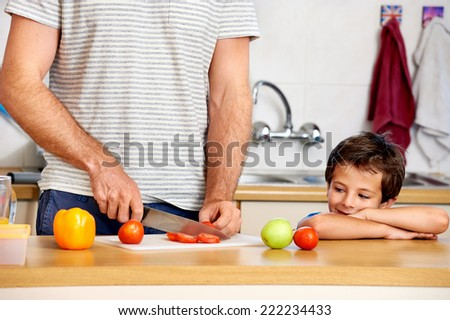 young boy watches dad prepare healthy food for school - stock photo