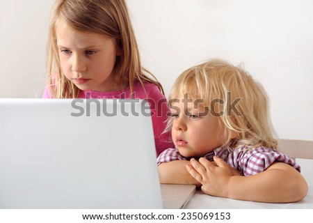 Young boy watches his sister playing a computer game on a laptop. He wishes he could play.  - stock photo