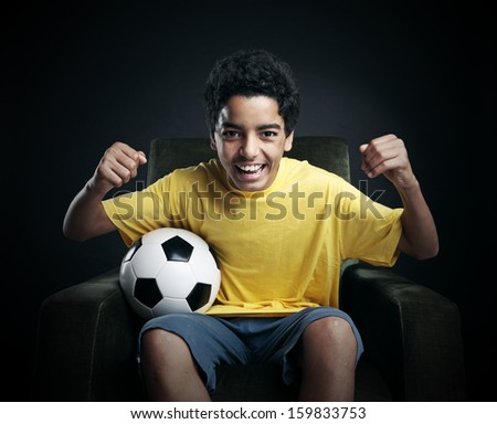 Young boy watching a soccer match on tv - stock photo