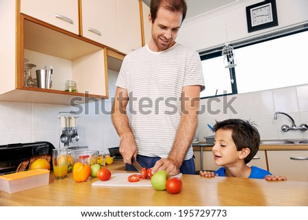 young boy watching father prepare healthy lunch - stock photo