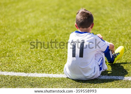 Young boy watching football match. Youth reserve player of football academy ready to play - stock photo