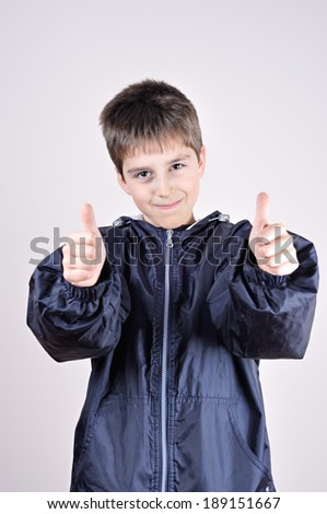 Young boy wearing blue jacket with thumbs up  - stock photo