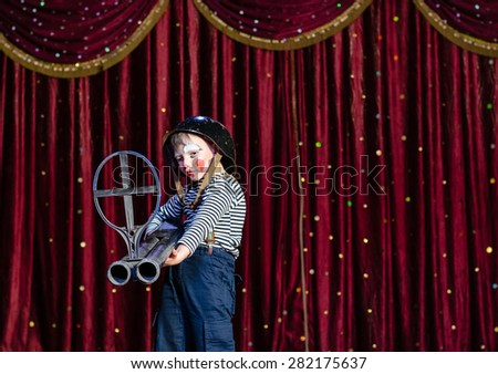 Young Boy Wearing Clown Make Up and Military Helmet Standing on Stage with Red Curtain Aiming Over Sized Prop Rifle Gun Toward Camera - stock photo