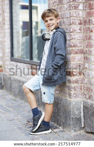 Young boy wearing headphones against wall, portrait  - stock photo