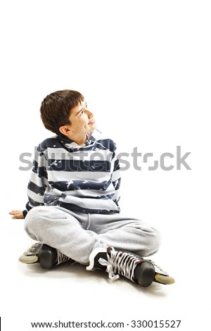 Young boy wearing roller skates sitting on floor, looking up. Isolated on white background - stock photo