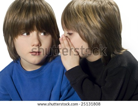 young boy whispers in his friend's ear - stock photo