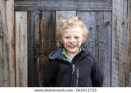Young boy with a barn wood background. - stock photo