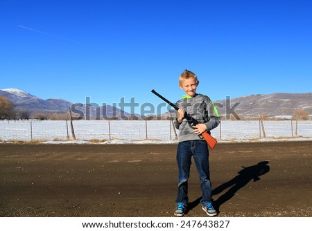 Young boy with a bb gun. - stock photo