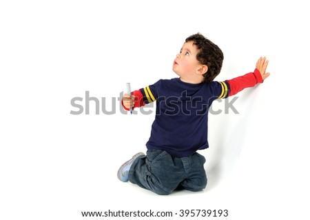 Young  boy with a blue marker preparing for wall painting - stock photo