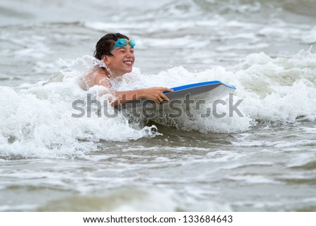 Young boy with a bodyboard on the beach - stock photo