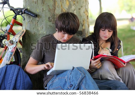 Young boy with a laptop computer sitting near a girl - stock photo