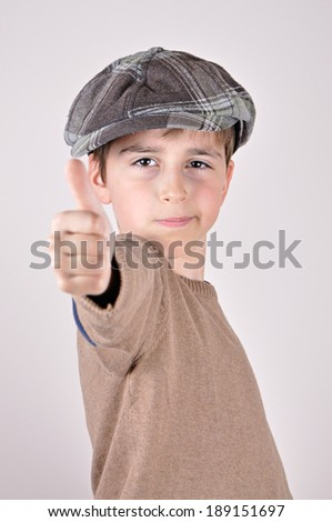 Young boy with a newsboy cap showing a thumb up - stock photo